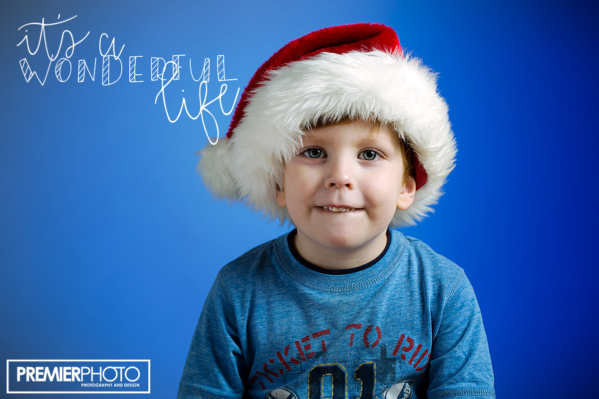 Young boy posing with Santa hat on a blue background