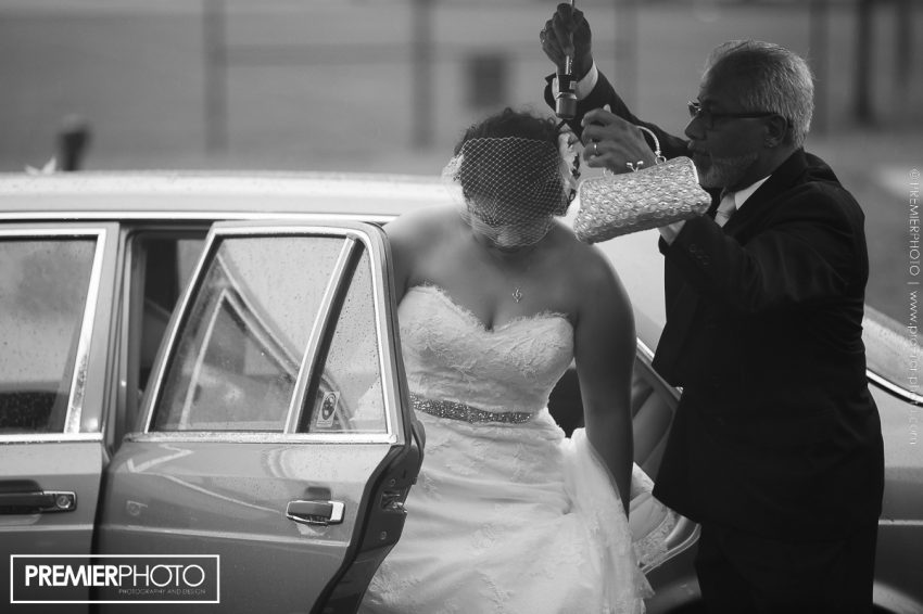 bride arriving at reception venue on a rainy day and helped out of the car by her father