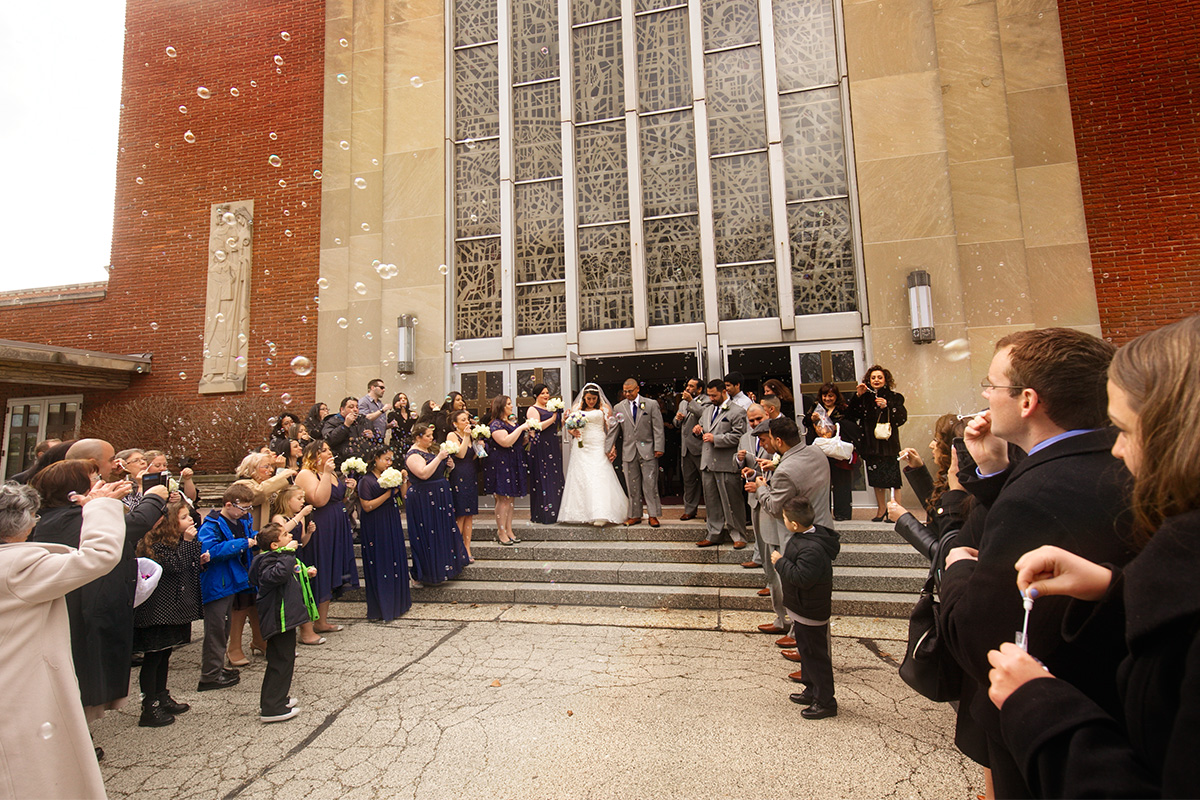 Exit shot of bride and groom after wedding ceremony with guests blowing bubbles